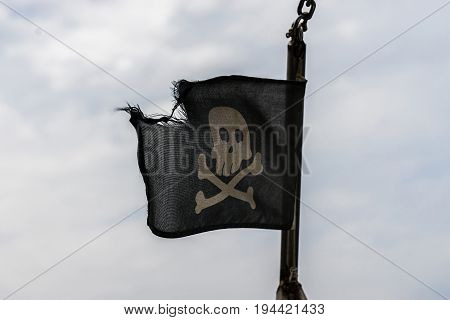 A Jolly Roger ragged flag in the wind