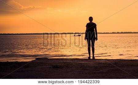 young woman stands on the stone bank of the estuary she looks at the passing boat and admires the beautiful evening