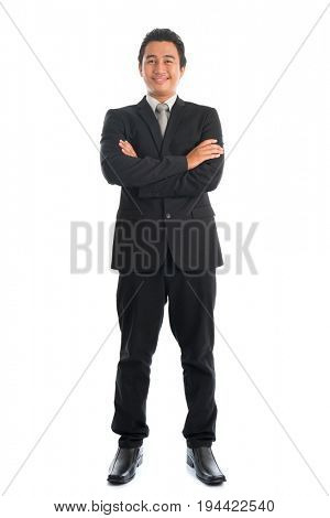 Full body arm crossed young Southeast Asian businessman standing isolated on white background.