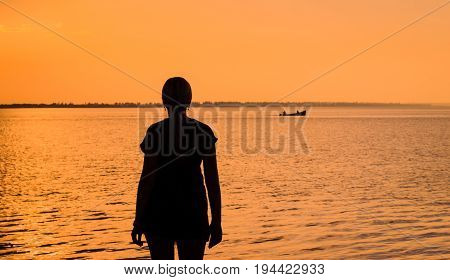 young woman admires the evening estuary on which the boat sails a warm summer atmosphere