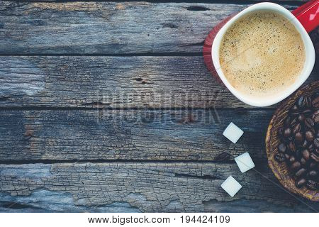 Bowl of roasted coffee beans red cup of coffee and sugar cubes on very old and rustic wood table background old time look dark tone big copy space