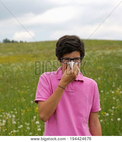 Allergic Boy With Glasses Blows His Nose Using A White Handkerch