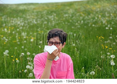Child With Allergy Blows His Nose In The Middle Of The Meadow Wi