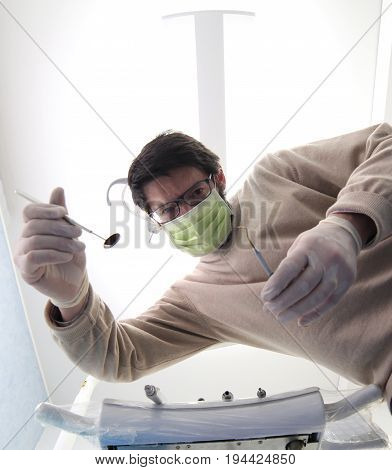 Medical dentist while examining the patient with medical instruments for oral cleansing