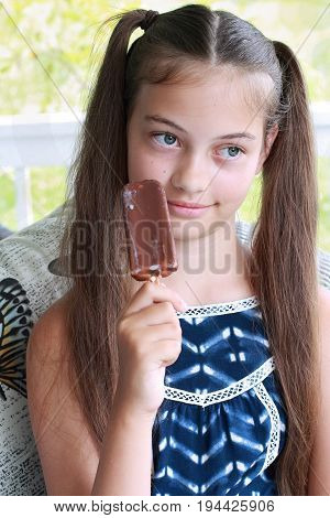 Young girl / child about to eat a chocolate ice cream on a stick.