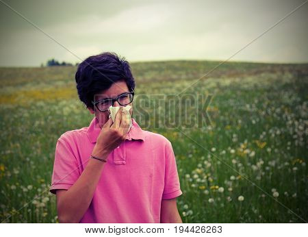 young boy wuith allergy blows his nose in springtime