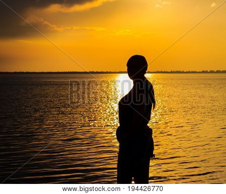 Silhouette of a young woman lit by a sunny path beautiful evening on a liman under a warm sky