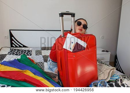 young woman with a Red suitcase Trips and recreation tourism. girl and a suitcase. beautiful female tourist with travel suitcase. girl and a bag