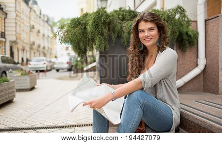 Travelgirl holding city map in hands. Young woman having planning her promenade with guidebook.