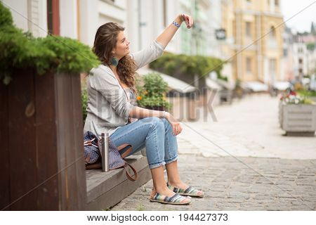 Tourist girl making selfie shot with mobile phone. Young and attractive woman, traveling, making selfie shots.