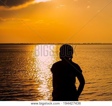 Silhouette of a posing young woman and a sunny path beautifully and brightly in the evening on the estuary before sunset