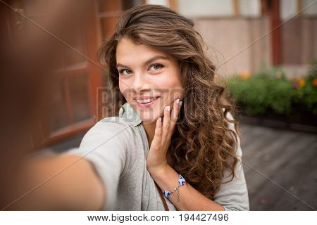 Selfie photo of young woman with flirty look. Travelgirl taking selfie shots in the street, picture made with wide open diaphragm.