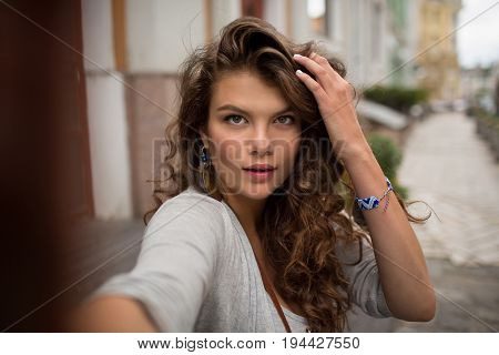 Tourist woman making selfie shot, touching her long brown hair. Young girl in the street of european city, taking selfie.