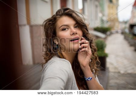 Selfie shot of young travel woman with nice street on the background. Beautiful girl with misterious look.