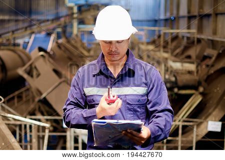 Engineer working in the production line of granular coal process plant, industrial concept