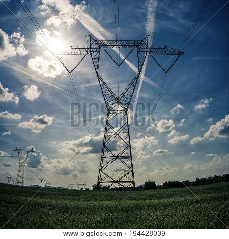 High voltage pylon with sun against blue sky
