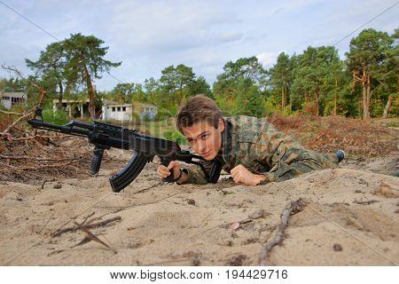 Teenager boy crawling in uniform and with a rifle Air Soft Gun