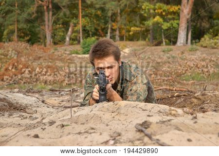 Teenager boy lying in his battle dress and a rifle Air Soft Gun