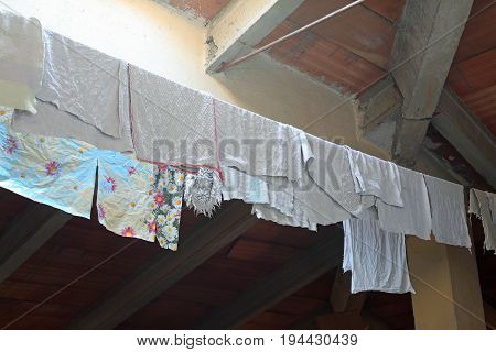Rags And Wet Canovars Hung To Dry In The Attic Of The House