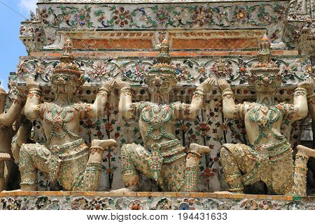 Giants at wat arun pagoda.  Pagoda with detail giants decoration The temple of sun rise near Choapraya river, Bangkok, Thailand.