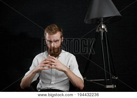 Portrait of serious confident young male photographer with thick red beard sitting on chair in his black studio having break during fashion photo shoot clasping hands and looking at camera