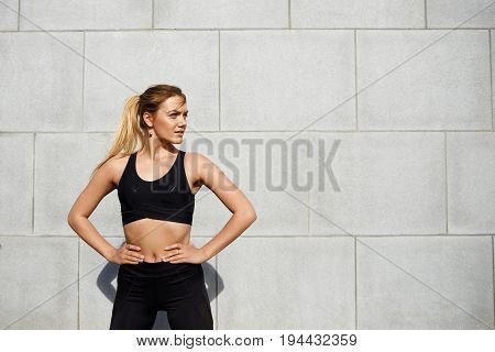 Attractive cute young female fitness instructor with ponytail dressed in black sportswear standing outdoors keeping hands on her waist making up her mind before workout class in the morning