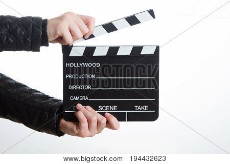 Close-up of hands of girl in black clothes is holding clapperboard on white background