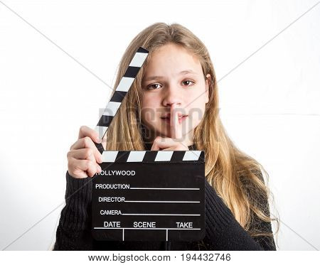 Teenage girl in black clothes, blonde with long hair is holding clapperboard, on white background