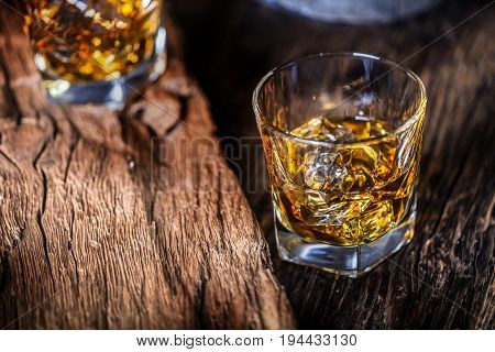 Whiskey drink. Whiskey drinks on rustic oak wood with ice cubes.