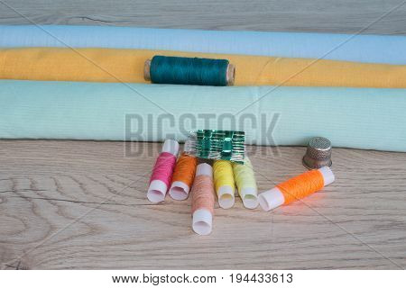 Sewing still life: colorful cloth. scissors and sewing kit includes threads of different colors thimble and other sewing accessories on wooden table. tools for sewing for hobby