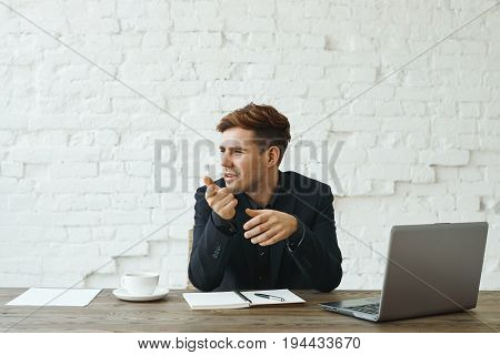 Attractive confident young recruiter sitting at office desk with open laptop computer copybook and papers looking sideways and pointing index finger at camera during job interview with applicant