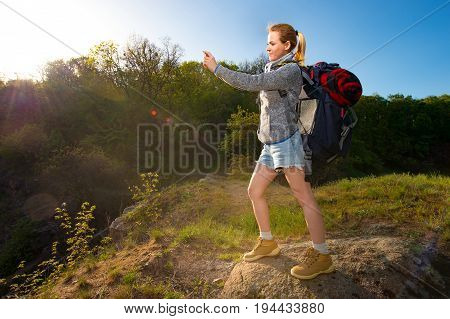 A young woman with backpack taking photo of beautiful landscape with her smartphone in a hike in the forest. Travel vacation holidays and adventure concept. Forest landscape background