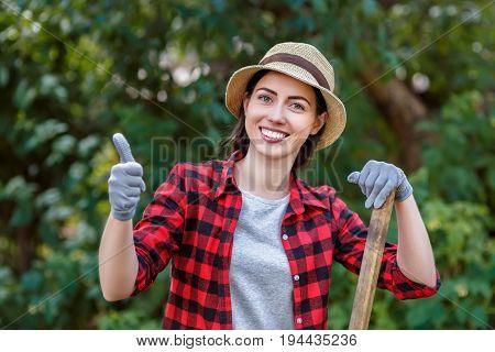 young woman gardener holding shovel in garden. People, gardening, planting, hobby concept
