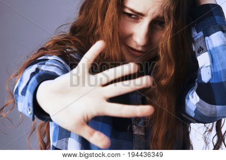 I am very afraid! Portrait of a young woman looking in fear with her hand in front of face (Gestures body language psychology)