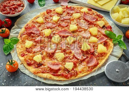 Fresh baked pizza hawaii with ham and pineapple, basil, tomatoes on backed paper.