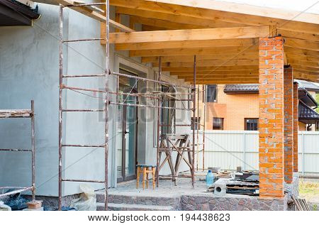 A private house is being constructed. Building a private house with red brick columns. Wooden beams for construction the roof