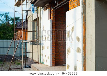 Construction of private house installing thermal insulation for walls with scaffolding