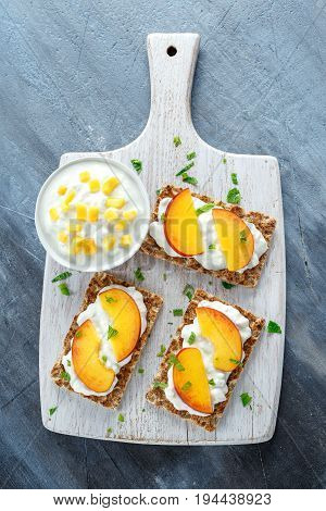 Homemade Crispbread toast with Cottage Cheese and nectarine on white wooden board