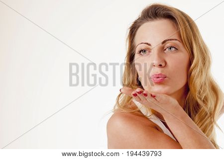 young beautiful woman sending air kiss (body language gestures psychology concept)