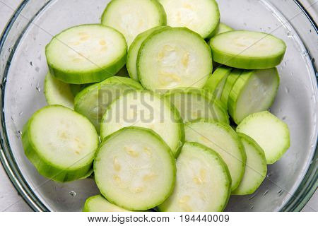 Green zucchini sliced in lobules in a glass plate