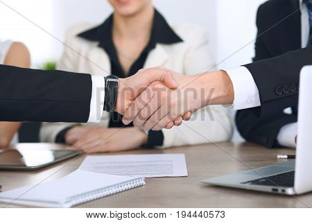 Close up of business people shaking hands at meeting or negotiation in the office. Partners are satisfied because signing contract.
