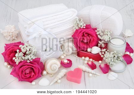 Natural spa beauty cleansing products with pink rose flowers, shells and pearls on distressed white wood  background.
