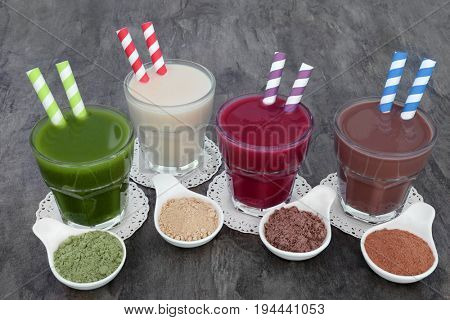 Health food supplement drinks of wheat grass, maca herb root, acai berry and chocolate whey with corresponding supplement powders in bowls. Also used by body builders.
