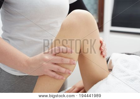 close up of Therapist applying pressure on female leg