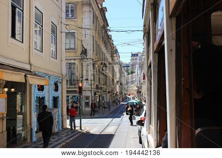 Traditional old town european portuguese street in Lisbon, Portugal, view from famous yellow tram window. Downtown Lisboa city architecture, historical apartments, lifestyle summer scene