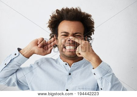 Afro American Dark-skinned Male Frowning His Face Holding Finger On Nose And Hand On Ear Trying To E