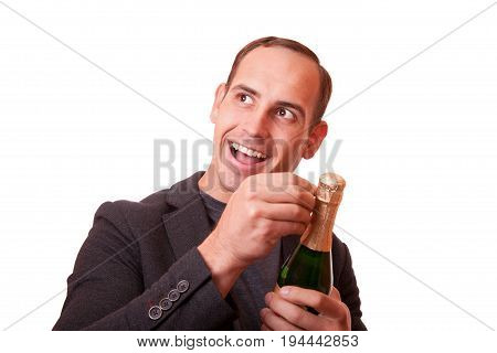 cheerful young man opens a bottle of champagne.