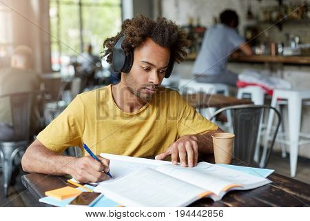 Hipster Afro American Guy Doing His Home Assigment Looking Attentively In Book And Copybook Listenin