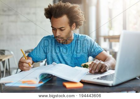 Candid Shot Of Concentrated Afro American Hipster Male In Blue T-shirt Preparing For Examination Tes