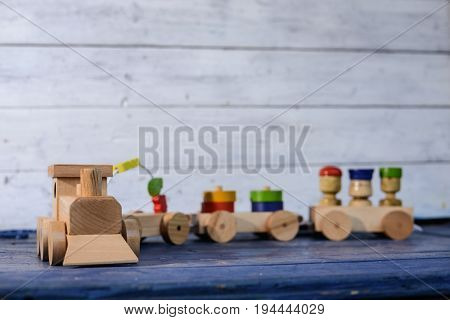 Colorful wooden freight train with loaded wagons